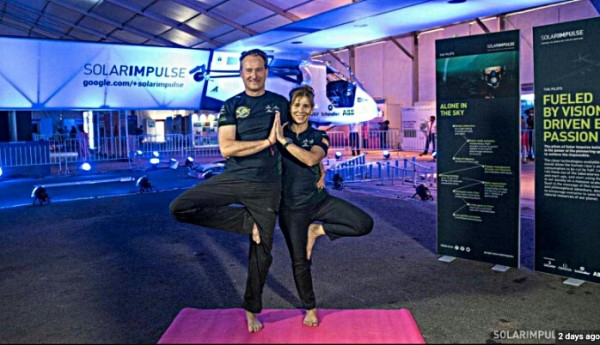 Solar Impulse Pilot Andre Borschberg doing yoga in front of Si2 solar plane. © Solar Impulse